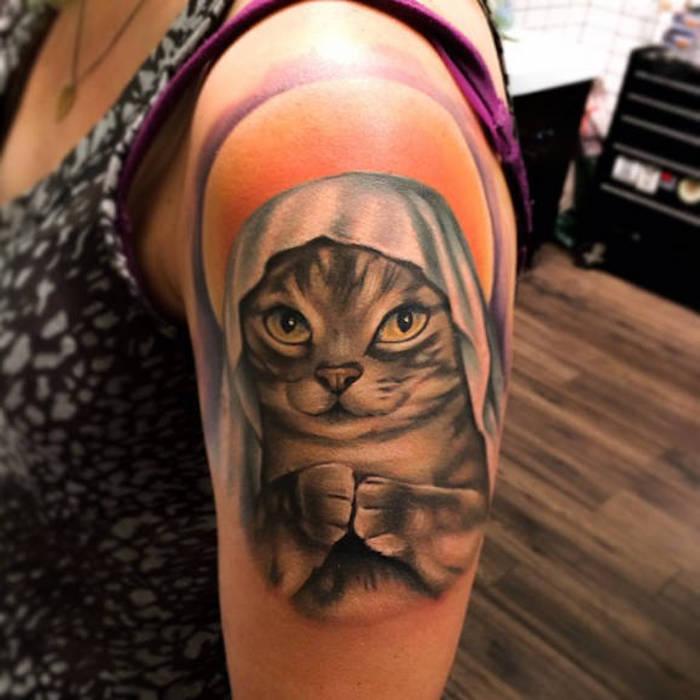 Tatuaggio gatto con occhi gialli sulla spalla di una donna