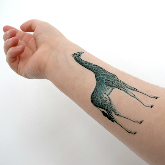 Idea per dei tatuaggi femminili, tattoo di una giraffa verde sull'avambraccio di una donna