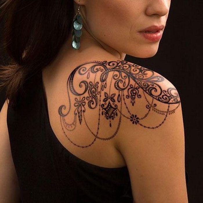 Donna con tatuaggi femminili sulla spalla, tattoo con motivi mandala