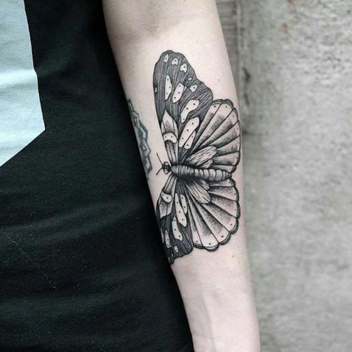 Tattoo simboli e farfalla, tatuaggio bianco e nero sull'avambraccio di una donna