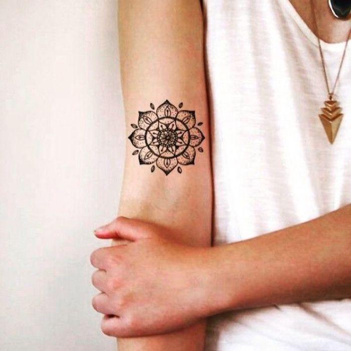 Tattoo con simboli mandala sull'avambraccio di una donna