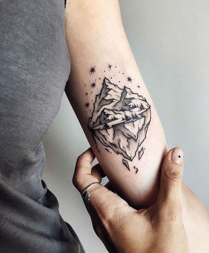 Idea per dei tatuaggi piccoli sulle braccia, disegno montagna con riflesso e stelle