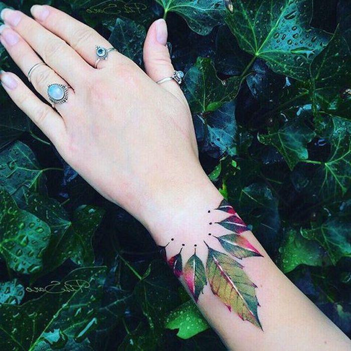 Tatuaggio colorato con disegno di foglie colorato sul polso della mano di una donna