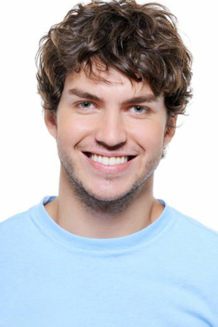 Uomo sorridente con i capelli mossi di colore castano scuro