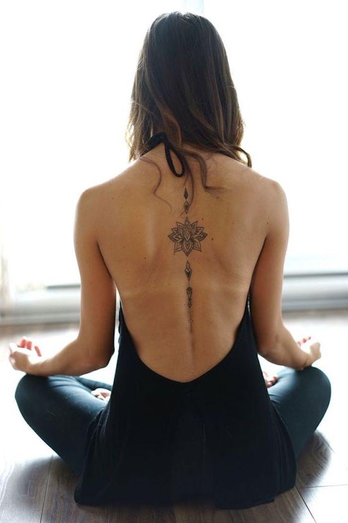Tattoo simboli e un grande tatuaggio mandala sulla schiena di una donna