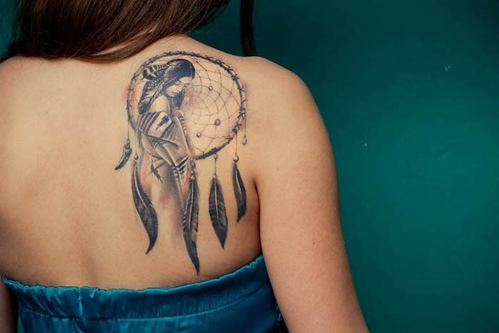 Disegni tatuaggi e un'idea con un acchiappasogni con piume sulla schiena di una donna
