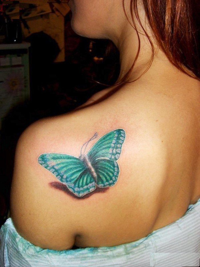 Farfalla di colore verde sulla schiena di una donna