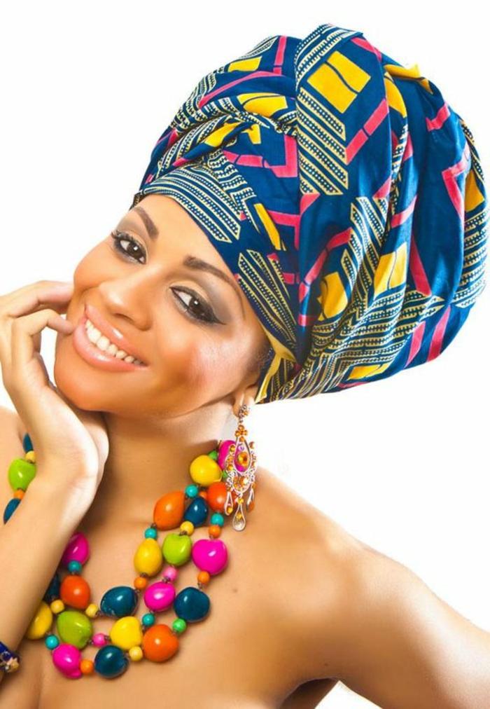 Ragazza sorridente, tessuti africani colorati, collana con pietre di diverso colore, sciarpa in testa