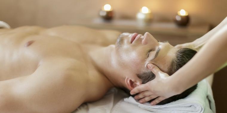 Un uomo con massaggio per il viso in una spa location con candele