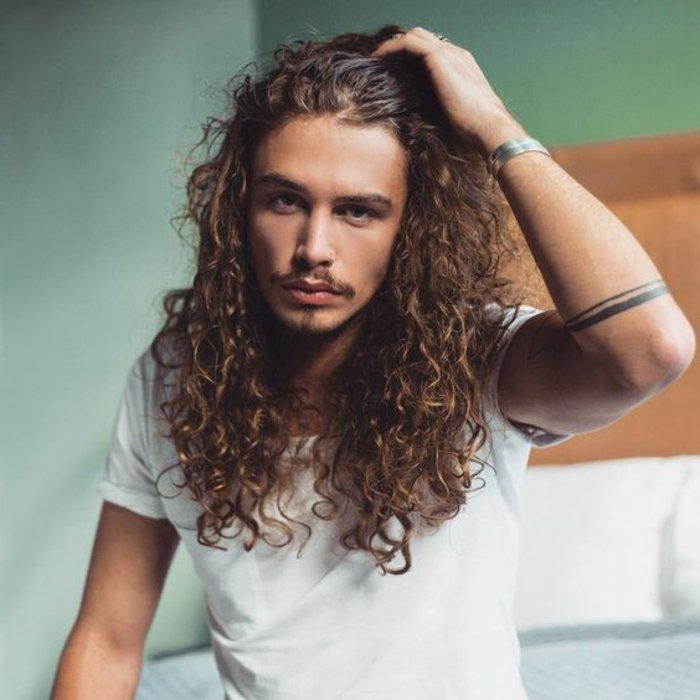 Pettinature uomo semplici con dei capelli molto lunghi e ricci di colore castano