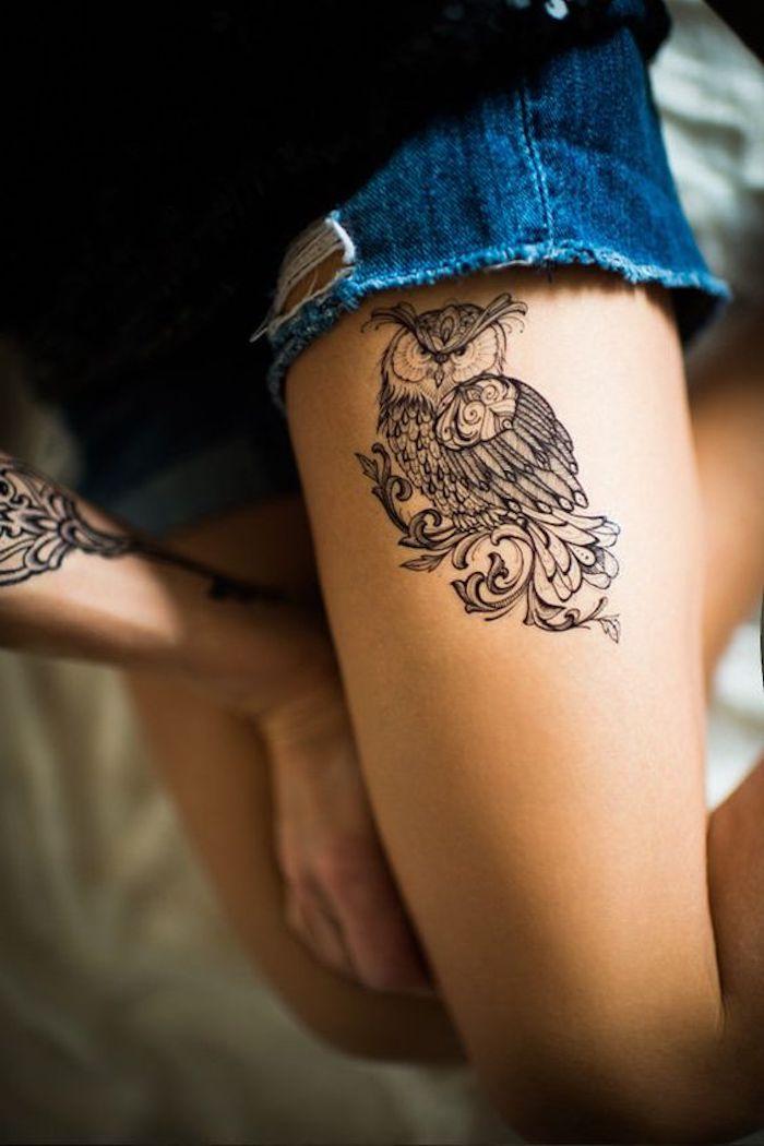 La coscia di una donna tatuata con un ufo e motivi mandala sul braccio