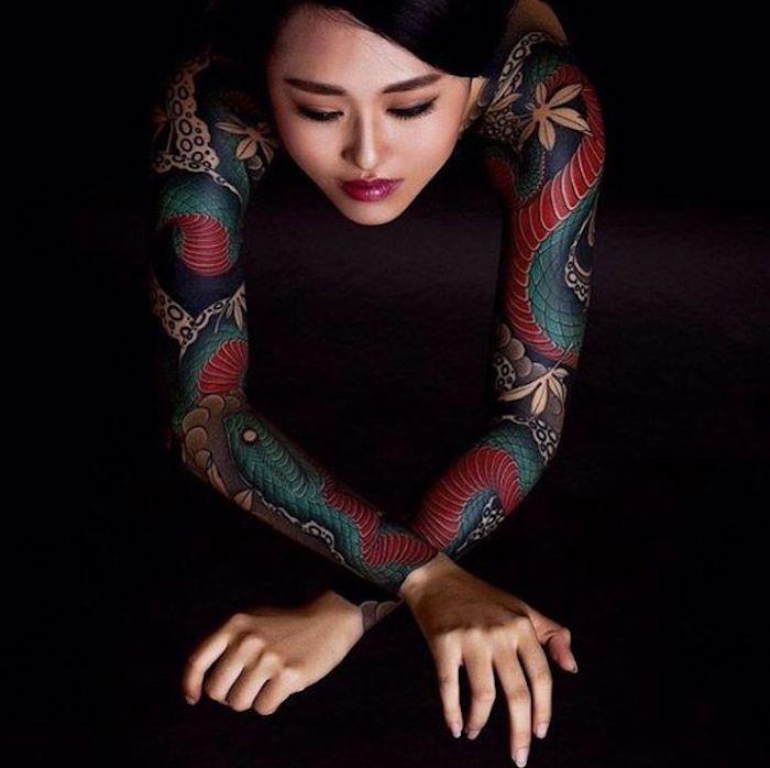 Un'idea per dei tatuaggi significativi sulle braccia, donna tatuata con motivi di pesce e serpenti