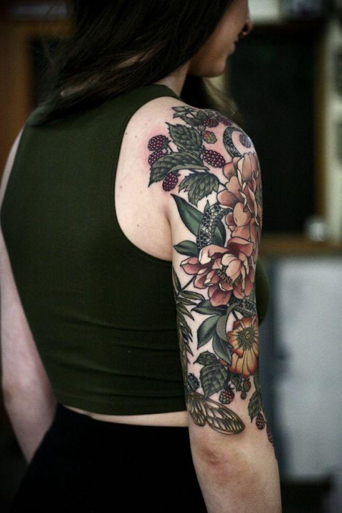Una donna girata di spalle con un tatuaggio sul braccio con fiori colorati