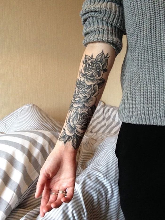 Il braccio di una donna con un grande tatuaggio floreale sul braccio