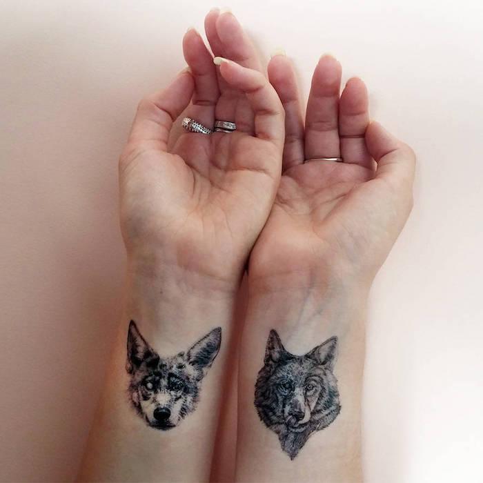 Due tatuaggi di animali con due cani sul polso della mano