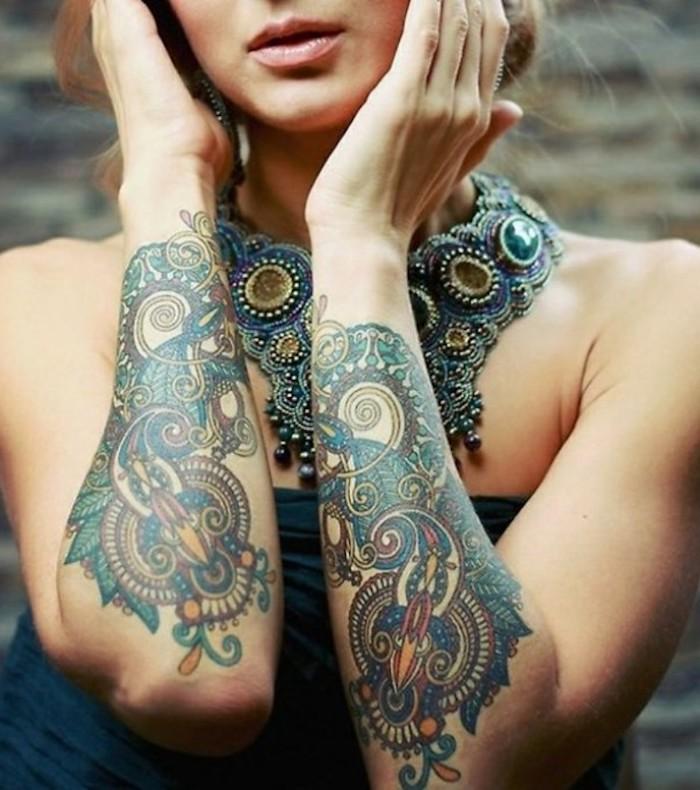 Tattoo simboli mandala colorati sulle braccia di una donna