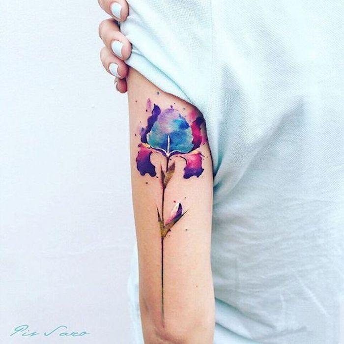 Tattoo simboli, tatuaggio temporaneo colorato di un fiore sul braccio di una donna