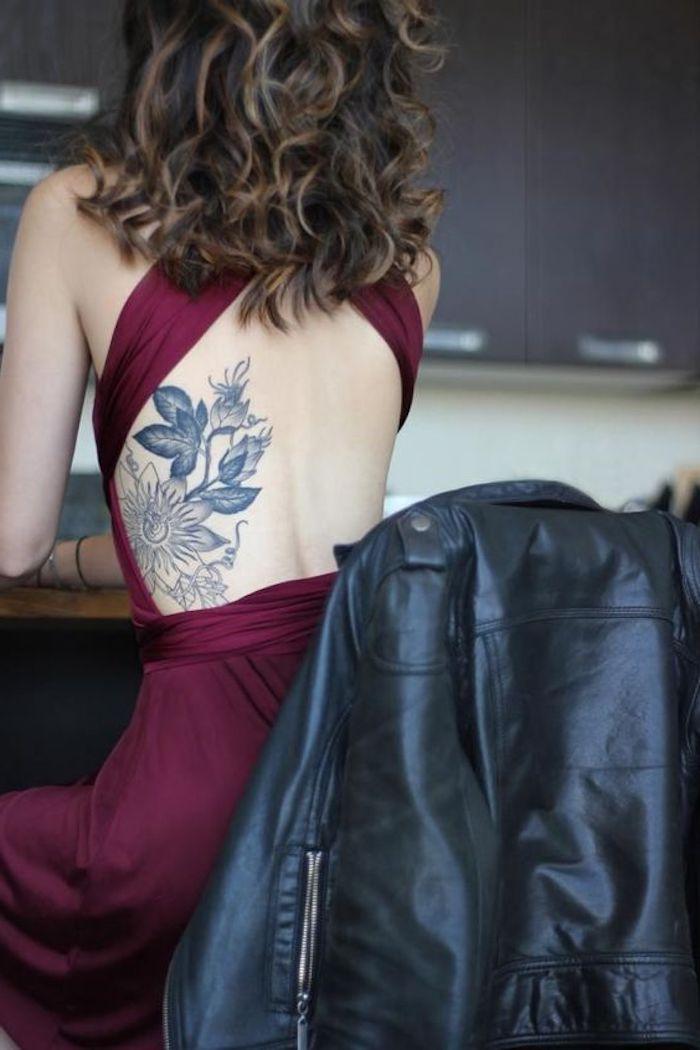 Un tatuaggio floreale sulla schiena di una donna vestita con un abito rosso