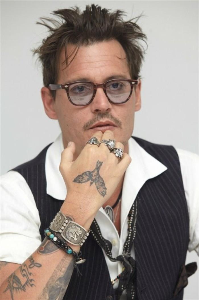 L'attore Johny Depp, tatuaggi stilizzati sul braccio, tattoo uccello sulla mano