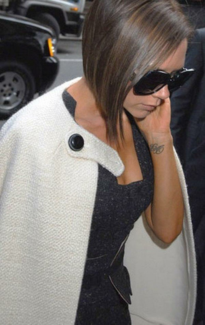 Taglio capelli caschetto corto, abbigliamento con giacca, tatuaggio sul polso della mano