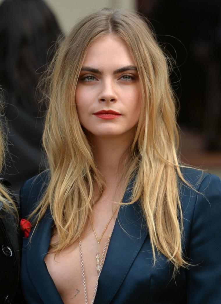 Cara Delevingne con capelli biondi, acconciature capelli media lunghezza, giacca blu con scollatura
