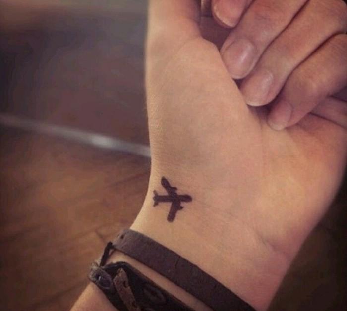 Tattoo particolari, tatuaggio aereo sul polso della mano, la mano di una donna