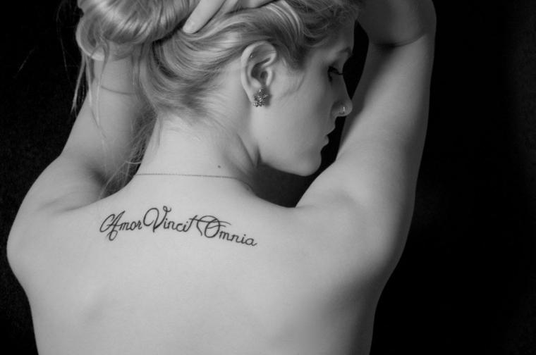 Tatuaggio Amor Vincit Omnia, tatuaggi piccoli scritte, donna con un tattoo sulla schiena