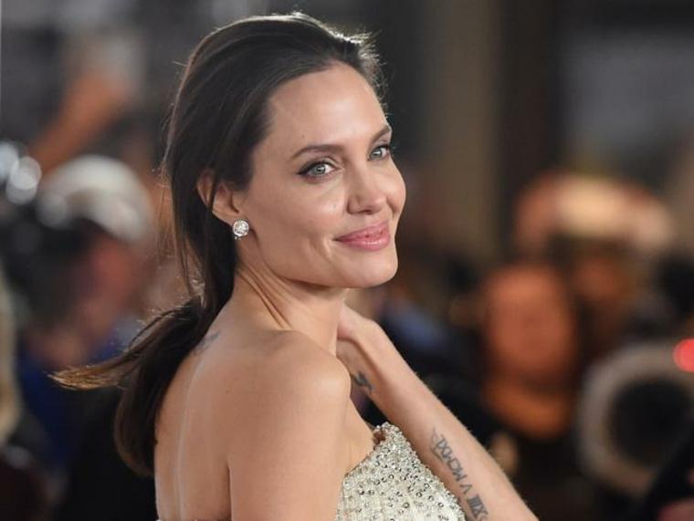 Tattoo con numeri romani, tatuaggi significativi profondi, Angelina Jolie con capelli sciolti