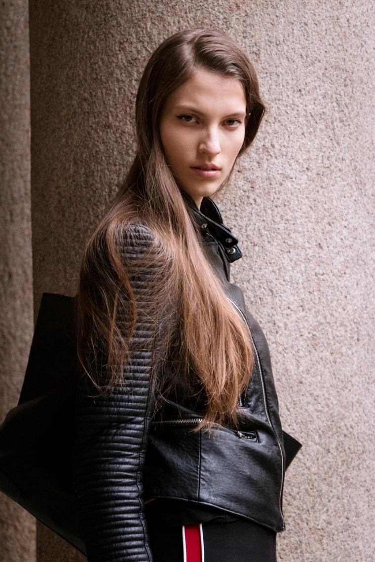 Ragazza con capelli castani, capelli lunghi e lisci, abbigliamento con giacca di pelle