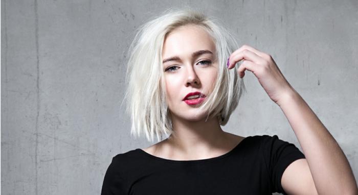 Ragazza bionda con taglio caschetto, pettinatura capelli effetto mosso, donna con una maglietta nera