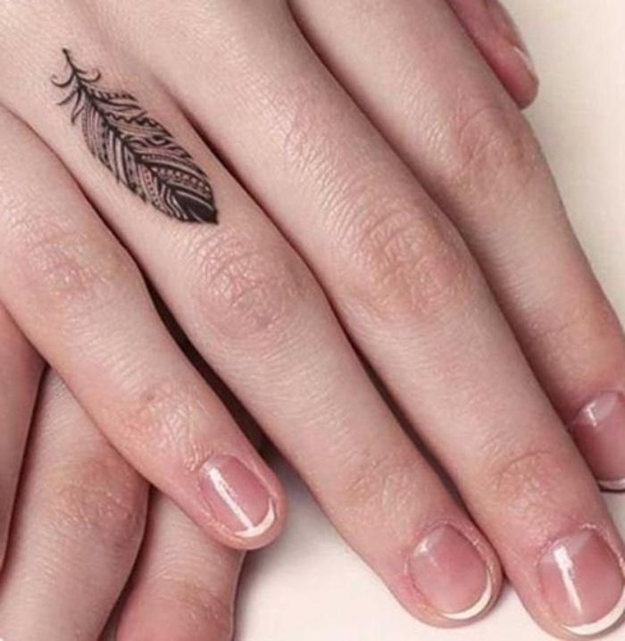 Tatuaggi più belli del mondo, tatto con disegno di una piuma, french manicure smalto bianco