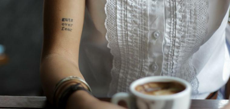 Tatuaggi piccoli scritte, donna con camicetta bianca, bere una tazza di cappuccino, tattoo sul braccio