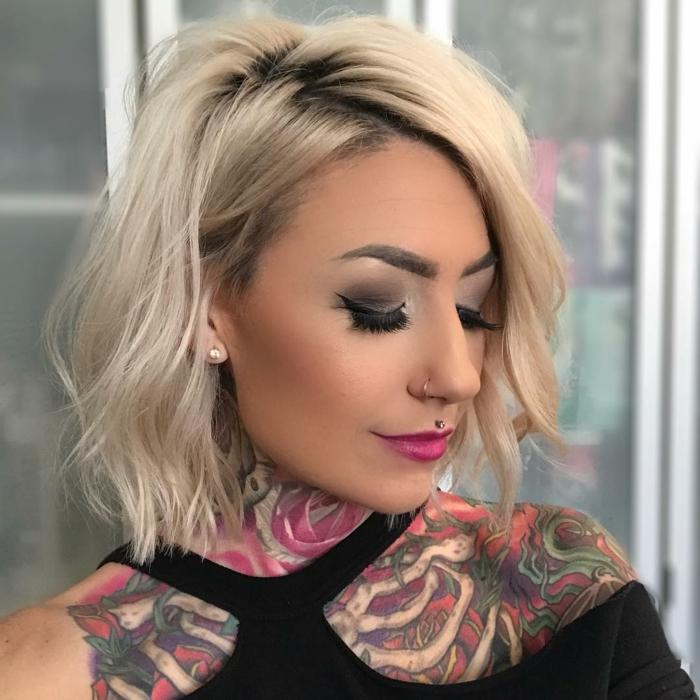 Ragazza con un taglio caschetto, capelli biondi mossi, ragazza con tatuaggi sulla spalla