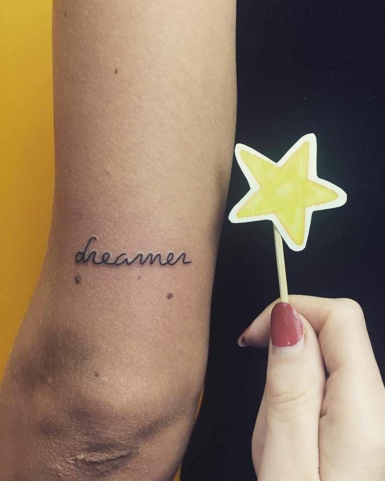 Tatuaggi scritte, tattoo sul braccio con lettere in corsivo, stella di cartoncino giallo