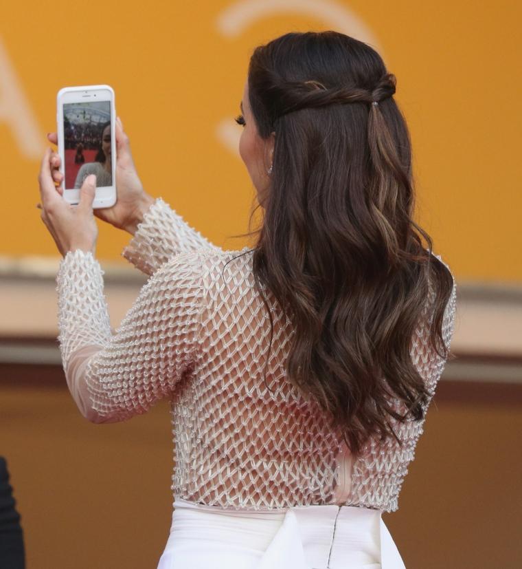 Capelli raccolti semplici, Eva Longoria che si fa il selfie, maglietta bianca trasparente