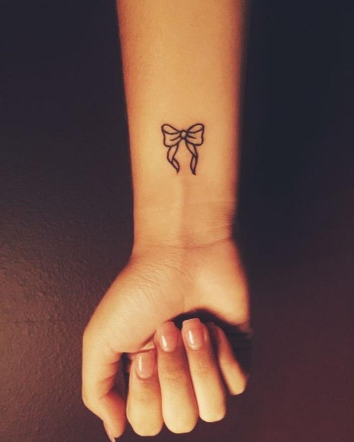 Tatuaggi avambraccio, tattoo disegno fiocco, donna con mano tatuata