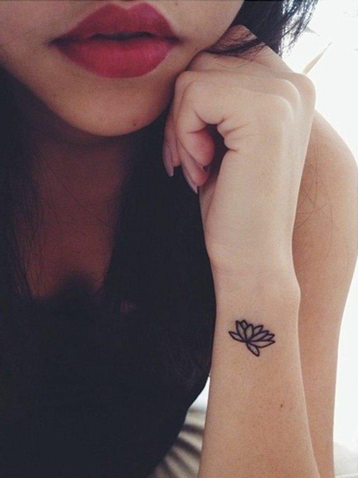 Disegno fiore di loto, tattoo polso della mano, labbra rosse di una ragazza