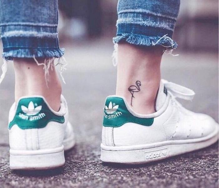 Catalogo tatuaggi, tattoo fiammingo sulla caviglia, donna con jeans