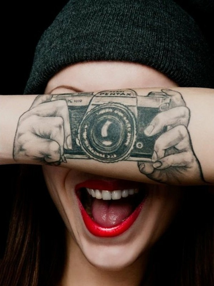 Frasi da tatuarsi, ragazza con rossetto rosso, tatuaggio fotocamera con mani, tattoo avambraccio donna