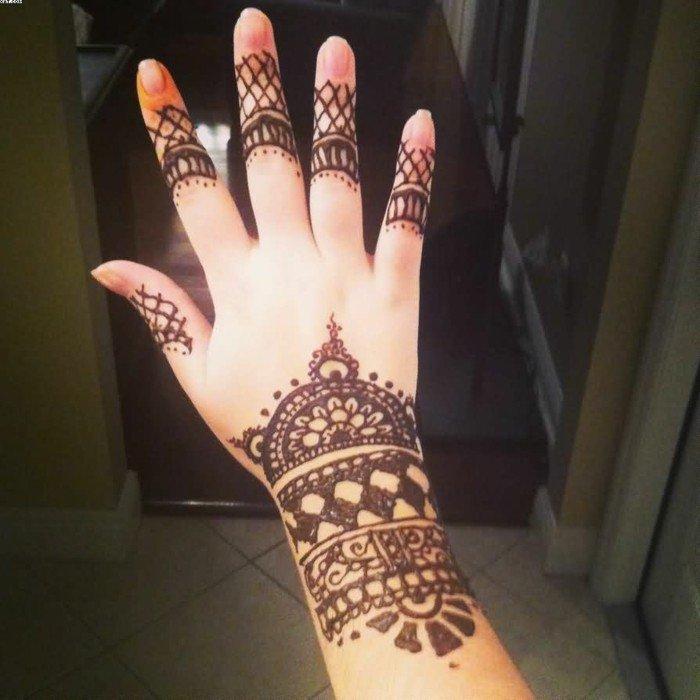 La mano di una donna, henna tatuaggio con simboli, smalto trasparente per unghie