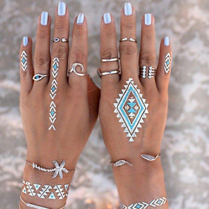 Manicure con smalto azzurro, tatuaggi henna sulle mano, anelli di metallo sulle dita