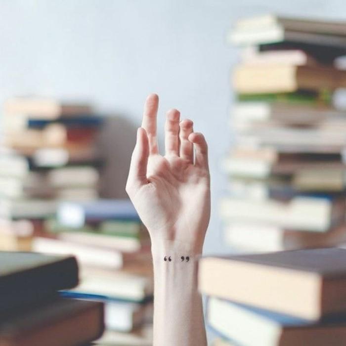 Tatuaggi belli sul polso della mano, la mano alzata di una donna, disegno virgolette sul polso