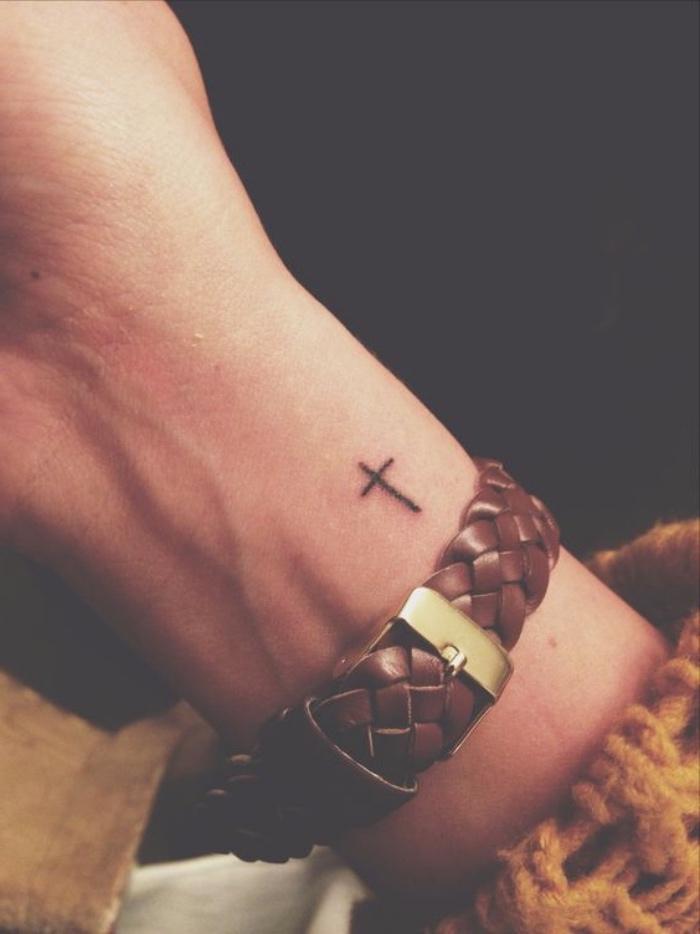 Tatuaggio piccolo, disegno croce sul polso, donna tatuata