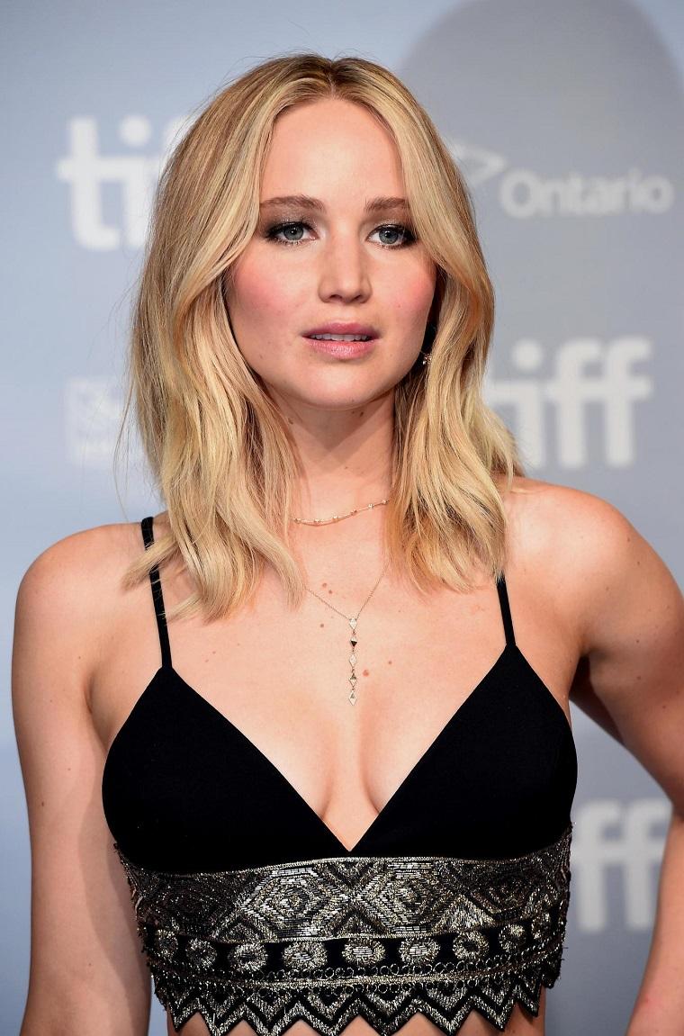 L'attrice Jennifer Lawrence, capelli biondi mossi, capelli medio corti, top corto colore nero