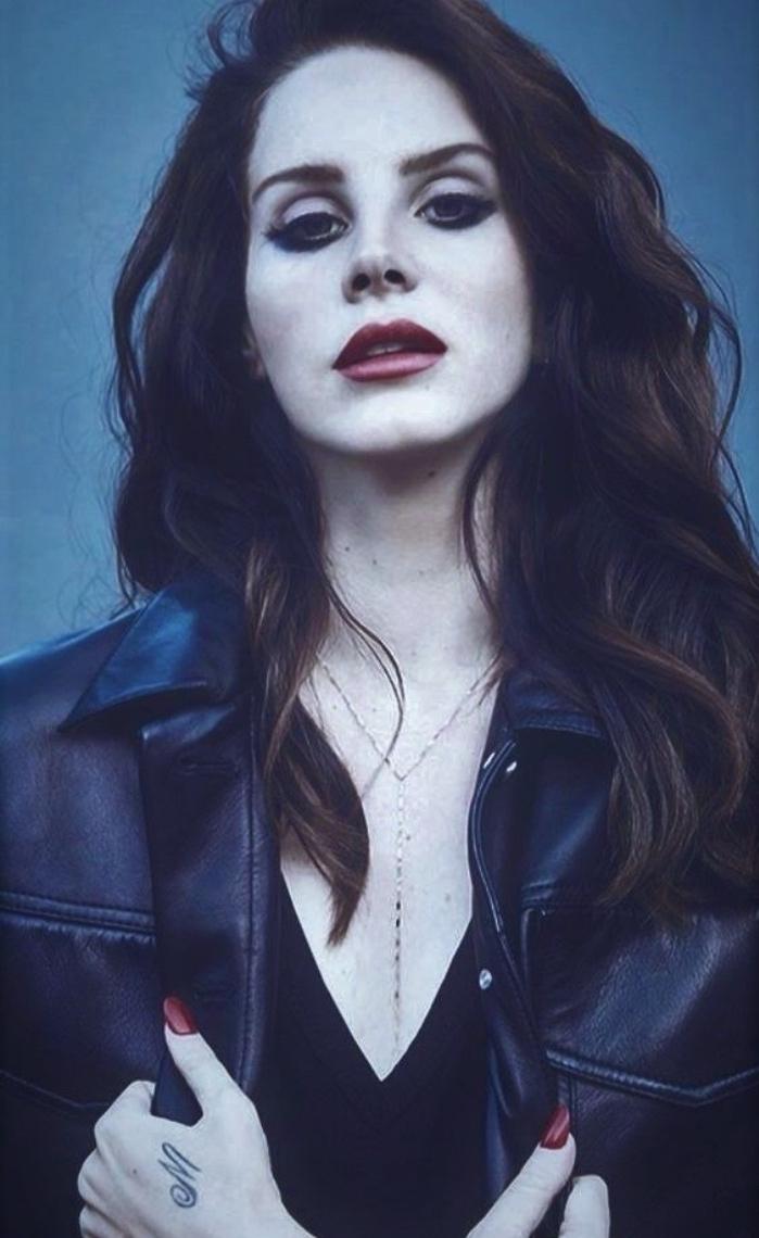 Tattoo scritte braccio, lettera M sulla mano, donna capelli lunghi, giacca di pelle nera
