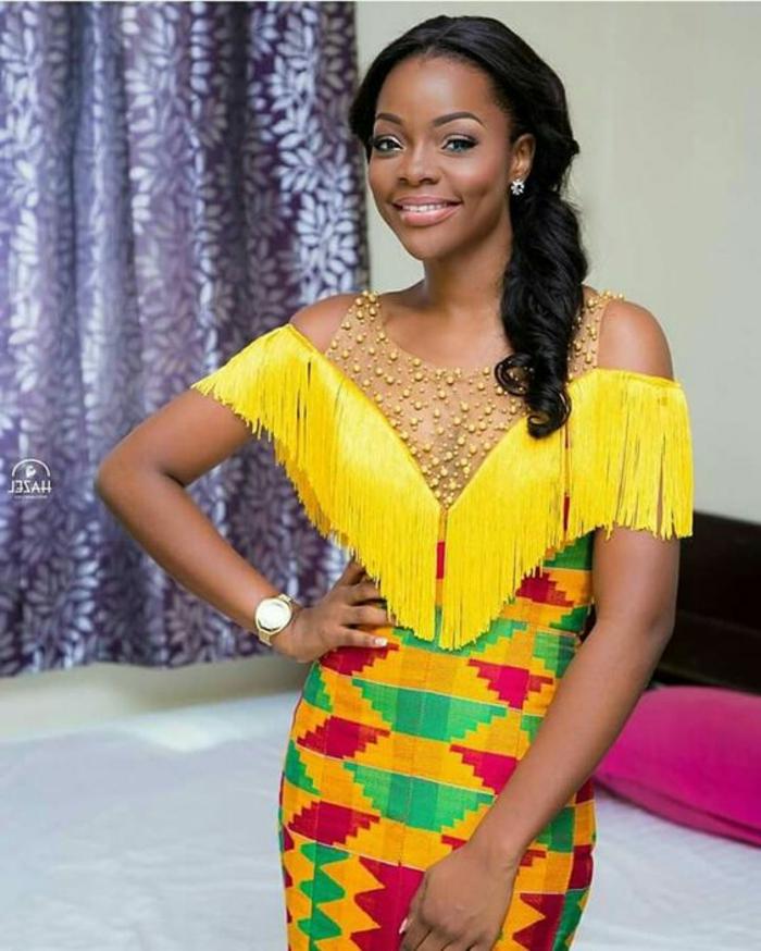 Stoffe africane con forme geometriche, abito tubino con frange gialle, ragazza con capelli neri ricci