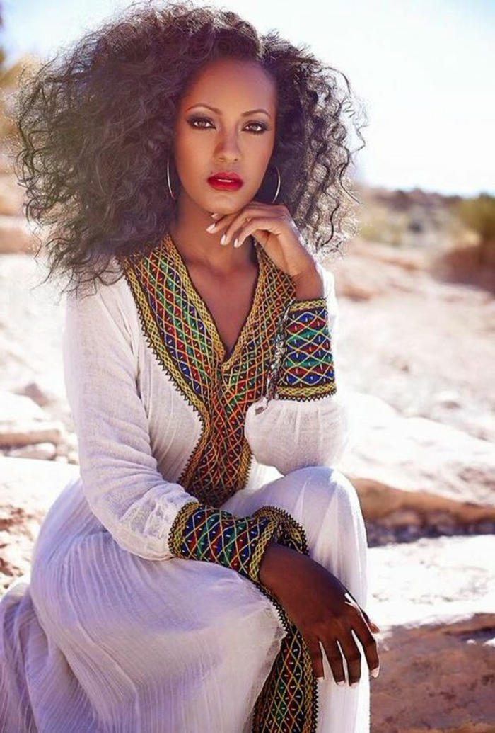 Moda femminile con abito bianco, vestito lungo con ricami colorati, capelli ricci di colore castano