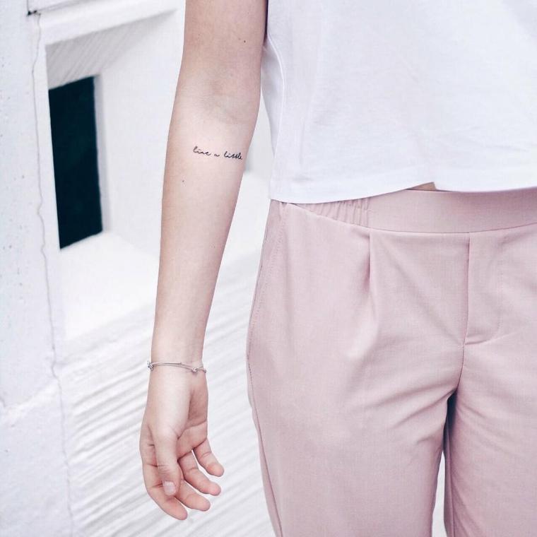 Donna con un pantalone rosa, frasi da tatuarsi, tatuaggio sull'avambraccio