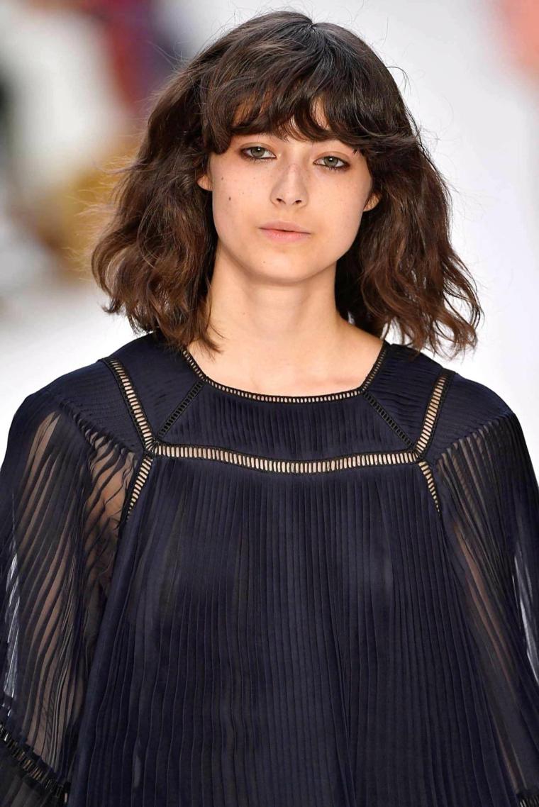 Donna con camicia nera trasparente, capelli caschetto mossi, acconciatura con frangia