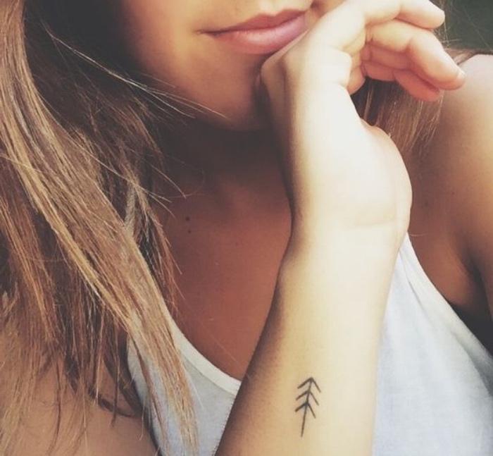 Tatuaggi stilizzati, disegno frecce, donna con tattoo sul polso